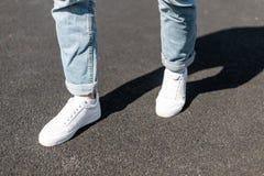 时髦的年轻人在皮革白色运动鞋的一条柏油路站立在时髦的蓝色牛仔裤 时兴的人的鞋子 免版税图库摄影