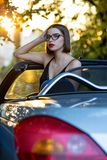 时髦的式样戴着眼镜,坐在有平衡阳光的金子的一辆敞篷车汽车 库存图片