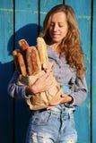 时髦的微笑白肤金发的妇女在他们的手上拿着与新鲜的长方形宝石的一个纸袋 免版税库存照片