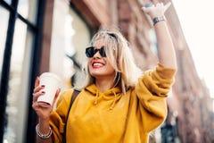 时髦的愉快的少妇佩带的boyfrend牛仔裤,白色运动鞋明亮的黄色运动衫 她拿着咖啡去 smil画象  库存图片