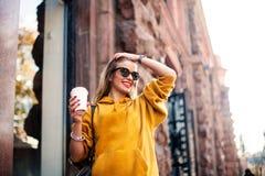 时髦的愉快的少妇佩带的boyfrend牛仔裤,白色运动鞋明亮的黄色sweetshot 她拿着咖啡去 smili画象  图库摄影