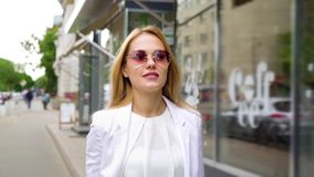 时髦的成套装备的俏丽的白肤金发的妇女步行沿着向下在慢动作的街道的 影视素材