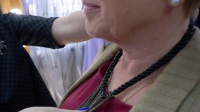 时髦的成熟妇女尝试的项链前面镜子在辅助部件陈列室里 帮助时尚的美发师尝试典雅 影视素材