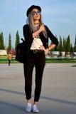 时髦的摆在街道上的白金白肤金发的妇女 图库摄影