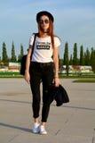 时髦的摆在街道上的白金白肤金发的妇女 免版税库存图片