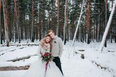 时髦的新娘和新郎与花束在多雪的森林冬天婚礼的背景摆在 库存照片