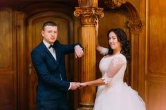 时髦的新娘和新郎家庭画象在富有的内部在老经典豪宅 库存图片