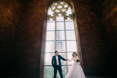 时髦的新娘和英俊的典雅的新郎跳舞在豪华内部背景与大窗口 免版税图库摄影