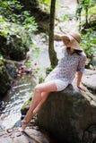 时髦的旅客女孩佩带的帽子和看河在晴朗的森林暑假 旅行和旅行癖概念 库存照片