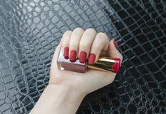 时髦的时兴的女性红色表面无光泽的修指甲,方形的形状 库存照片