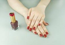 时髦的时兴的女性红色表面无光泽的修指甲,方形的形状 库存图片