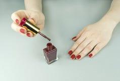 时髦的时兴的女性红色表面无光泽的修指甲,方形的形状 免版税库存照片