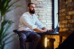 时髦的有胡子的男性与膝上型计算机一起使用 免版税库存图片