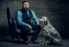 时髦的有胡子的男性坐椅子和爱尔兰人的特定装置狗 免版税库存图片