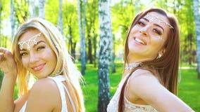 时髦的服装的白肤金发和深色的女性舞蹈家在桦树中的阳光下 股票录像