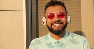 时髦的桃红色太阳镜的听到在耳机的音乐的年轻情感非洲人的特写镜头画象和 股票视频
