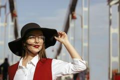 时髦的模型时尚画象穿红色服装,黑帽会议, 免版税库存照片
