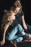 时髦的母亲和女儿坐在黑色的立方体 库存图片