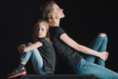 时髦的母亲和女儿坐在黑色的立方体 图库摄影