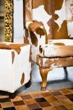 时髦的母牛皮肤皮革扶手椅子 图库摄影