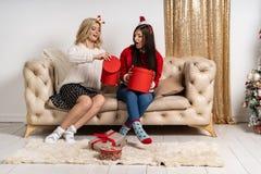 时髦的毛线衣和圣诞老人帽子的两个年轻愉快的女孩 免版税图库摄影