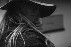 时髦的浅顶软呢帽的单色金发碧眼的女人 库存图片