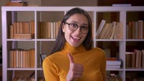 时髦的深色的女老师画象打手势赞许标志显示象和在图书馆尊敬 股票录像