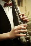 时髦的演奏在o背景的行家坐的人单簧管  免版税库存图片
