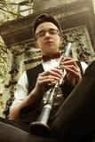 时髦的演奏在o背景的行家坐的人单簧管  图库摄影