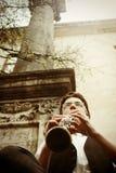 时髦的演奏在o背景的行家坐的人单簧管  库存图片