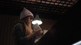 时髦的玻璃和帽子的一位行家女性在咖啡馆选择茶 影视素材