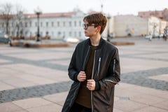 时髦的玻璃的时兴的年轻行家人与在一件时兴的长的黑夹克的一种时髦的发型在T恤杉 免版税库存图片