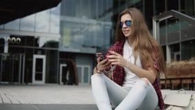 时髦的玻璃的美丽的30s妇女坐步临近现代大厦和听的音乐 影视素材