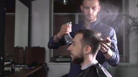 时髦的男性在客户和掠过它的头发的理发师喷洒的水的图象做时髦的理发 年轻美发师 股票视频