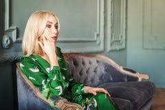 时髦的白肤金发的妇女在家坐沙发 库存图片