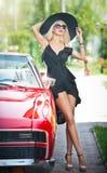 时髦的白肤金发的葡萄酒妇女夏天画象有摆在红色减速火箭的汽车附近的长的腿的 时兴的可爱的公平的头发女性 免版税库存照片