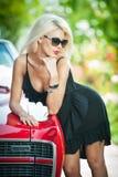 时髦的白肤金发的葡萄酒妇女夏天画象有黑太阳镜的弯曲了在减速火箭的汽车 时兴的可爱的公平的头发女性 库存图片