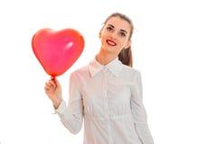 时髦的白色T恤杉的年轻逗人喜爱的深色的妇女有红色心脏的在看起来她的被隔绝的手去和微笑上  免版税库存图片