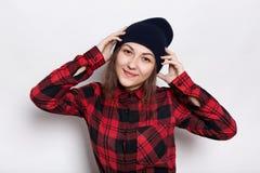 时髦的盖帽的行家女孩在红色有被检查的衬衣穿戴了握她的在头的愉快的表示手在白色 免版税图库摄影