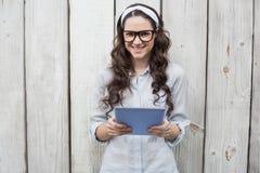 戴时髦的眼镜的时髦少妇使用片剂个人计算机 免版税库存图片
