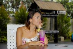 时髦的礼服的喝健康果汁的年轻美丽和性感的亚裔妇女在度假胜地咖啡店或餐馆 图库摄影