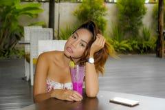 时髦的礼服的喝健康果汁的年轻美丽和性感的亚裔妇女在度假胜地咖啡店或餐馆 库存照片