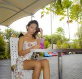 时髦的礼服的喝健康果汁的年轻美丽和性感的亚裔妇女在度假胜地咖啡店或餐馆 库存图片