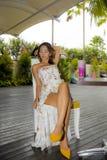 时髦的礼服的喝健康果汁的年轻美丽和性感的亚裔妇女在度假胜地咖啡店或餐馆 免版税库存照片