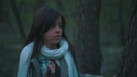 时髦的神色的小欧洲深色的女孩 害怕孤独的女孩在黑暗的森林里想知道,她看 股票录像