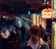 时髦的红头发人女孩身分在街道上的夜 有启发性牌,氖,光 免版税库存图片