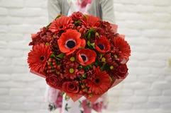 时髦的红色花束在女孩的手上 库存图片
