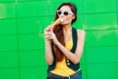 时髦的美丽的女孩用冰淇凌在绿色金属附近站立 库存图片