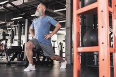 时髦的老男性享受在现代健身房的锻炼 库存图片