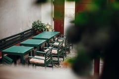 时髦的老绿色木桌和椅子在咖啡馆大阳台在PR 库存图片